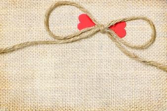 Großer Bogenseilsack mit rotem Herzpapier der Paare auf braunem Sackhintergrund haben Kopienraum für p