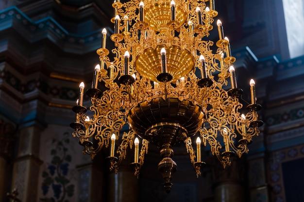 Großer bronze-kronleuchter mit elektrischen kerzen in der christlichen kirche der kathedrale. selektiver fokus