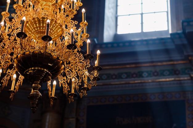 Großer bronze-kronleuchter mit elektrischen kerzen in der christlichen kirche der kathedrale. tageslicht aus dem fenster in der kirche. selektiver fokus