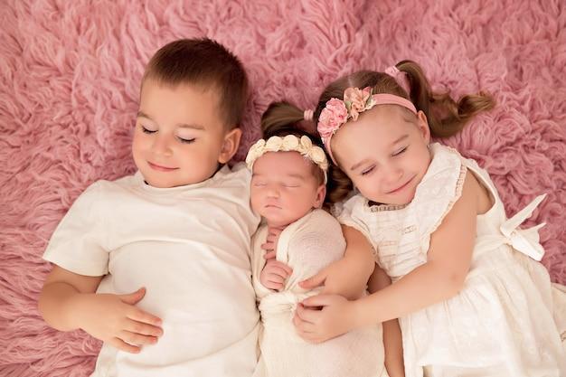 Großer bruder und schwester mit kleiner neugeborener schwester