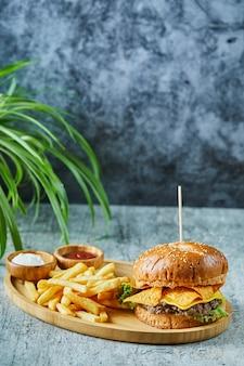 Großer burger mit bratkartoffel in der holzplatte auf der marmoroberfläche