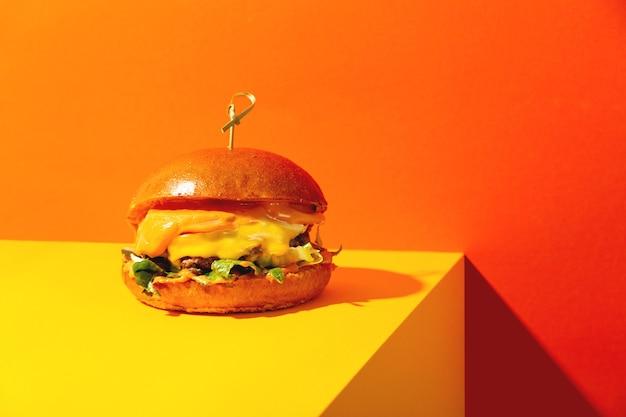 Großer burger mit käse auf leuchtend orangefarbenem und gelbem hintergrund amerikanische fastfood-küche in einem modernen...