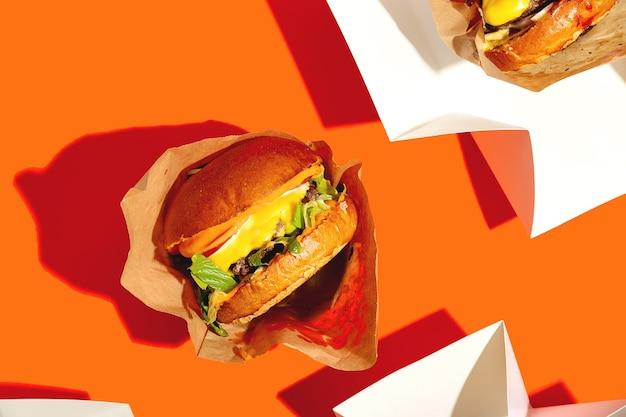Großer burger mit käse in einem paket auf einem leuchtend orangefarbenen hintergrund fastfood-lieferung