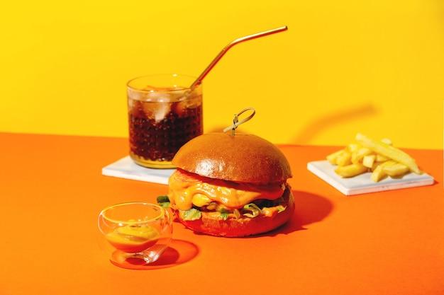 Großer burger mit pommes frites und sauce auf leuchtend orangefarbenem und gelbem hintergrund amerikanisches fast-food-küche...