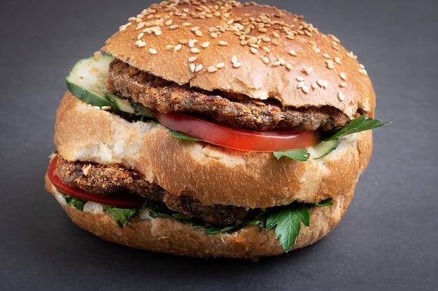 Großer burger mit zwei koteletts, tomate, kopfsalat und käse, nahaufnahme