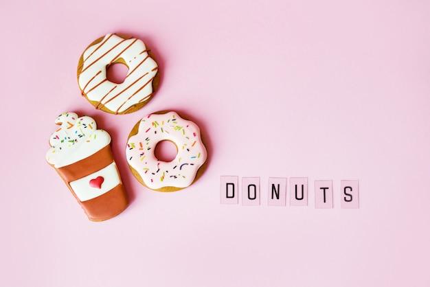 Großer donut- und lebkuchendonut auf rosa oberflächengeburtstagsdekoration