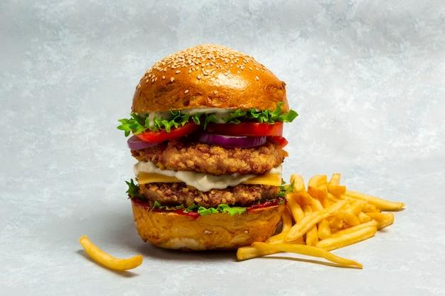 Großer doubleburger mit paniertem hähnchenschnitzel und pommes