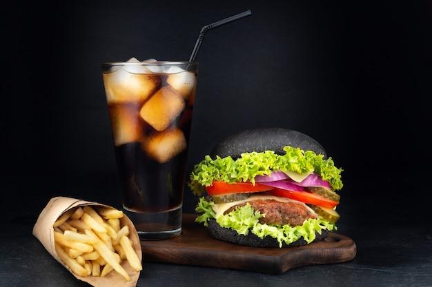 Großer einzelner cheeseburger mit einem glas cola und pommes frites