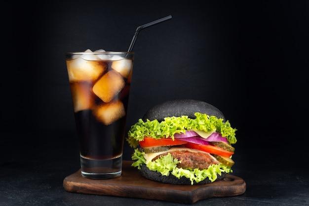 Großer einzelner cheeseburger mit glas cola
