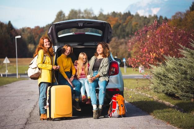 Großer familienausflug - glückliche mädchen reisen mit dem auto. mama mit töchtern im kofferraum sitzen