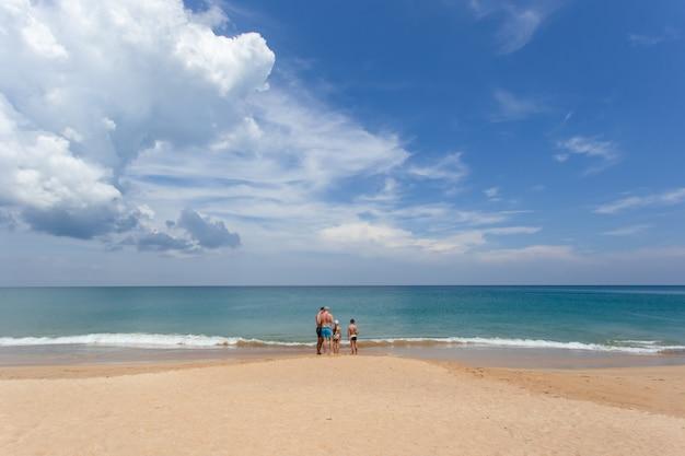 Großer familientourist auf weißem sandstrand bei mai khao beach