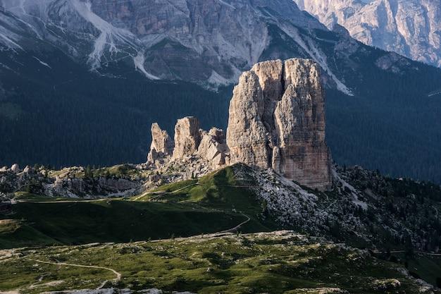 Großer felsen auf einem grasbewachsenen hügel mit bewaldeten bergen