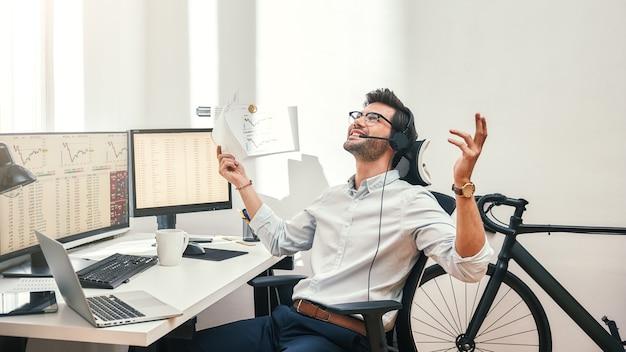 Großer glücklicher und erfolgreicher bärtiger händler im headset, der einen finanzbericht im gespräch mit dem kunden hält