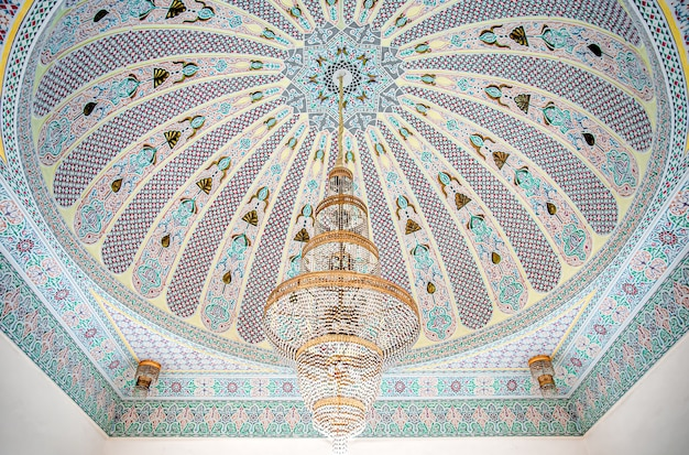 Großer goldener kronleuchter auf einer bunten decke mit islamischer traditioneller religiöser verzierung.