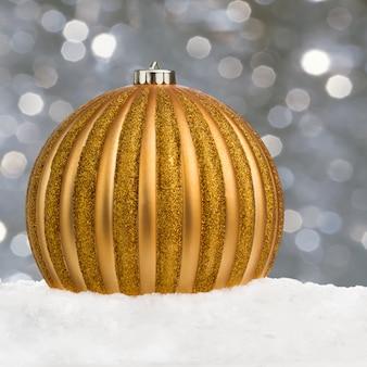 Großer goldener weihnachtsball auf schnee über festlichem defocused hintergrund mit kopieraum