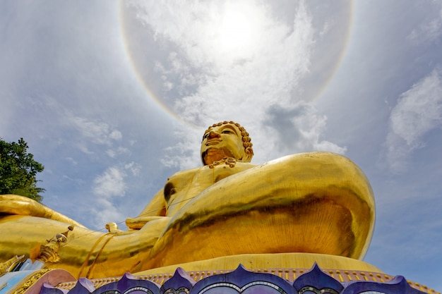Großer goldstatuenbuddha unter dem korona-ringsonnenlicht.