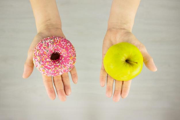 Großer grüner apfel und rosa donut in der hand. das konzept des diätvergleichs.