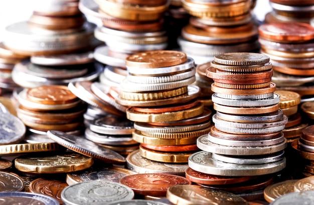 Großer haufen von spalten von verschiedenen münzen auf weißem hintergrund. kann als symbol für die steigerung des wohlstands verwendet werden.
