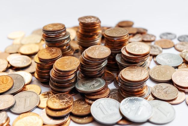 Großer haufen von spalten von verschiedenen russischen münzen auf weißem hintergrund.