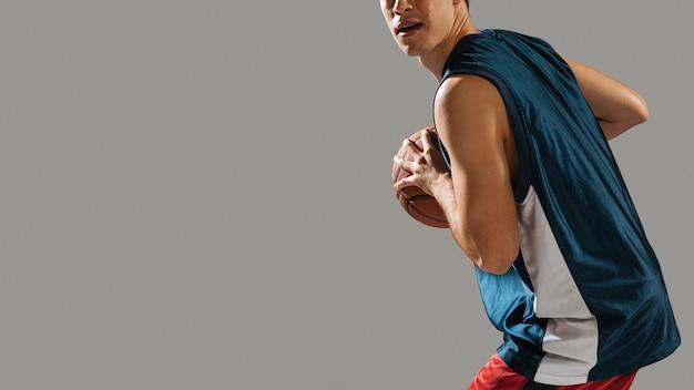 Großer junger mann, der basketball mit kopienraum spielt