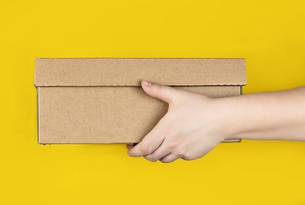 Großer karton in händen mit gelbem hintergrund