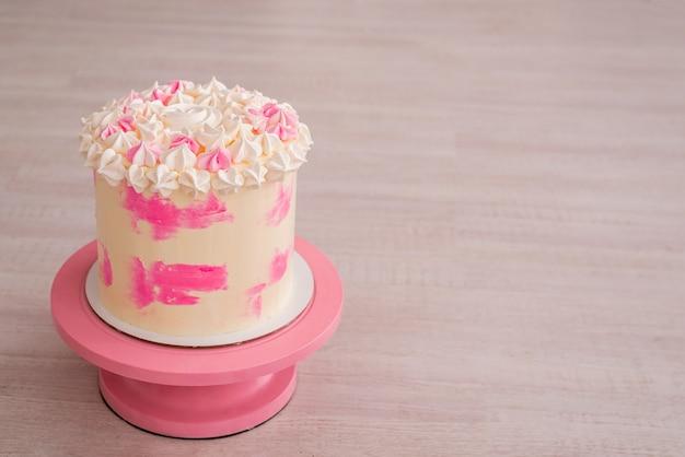 Großer kuchen mit rosa sahne und baiser. zarte geburtstagstorte für ein mädchen auf einem hölzernen hintergrund. .