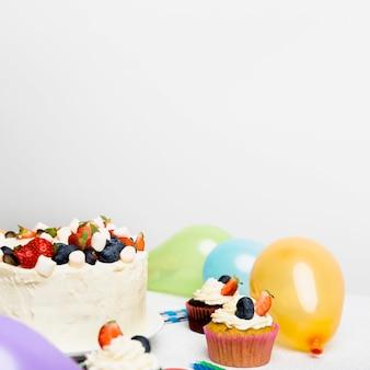 Großer kuchen mit verschiedenen beeren in der nähe von cupcakes