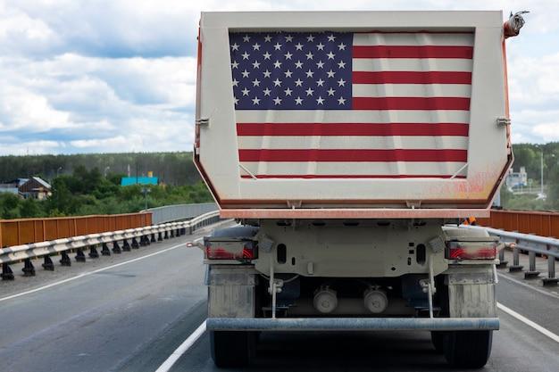 Großer lkw mit der nationalflagge der usa, die auf der autobahn bewegt,