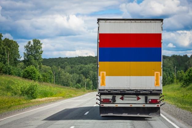 Großer lkw mit der nationalflagge von armenien, die auf der autobahn bewegt