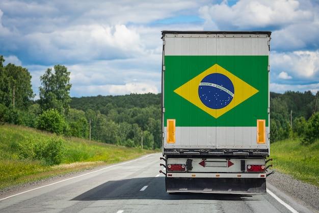 Großer lkw mit der nationalflagge von brasilien, die auf der autobahn bewegt