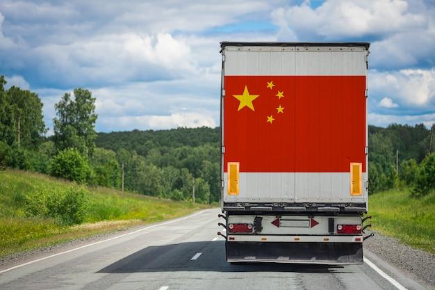 Großer lkw mit der nationalflagge von china, die auf der autobahn bewegt