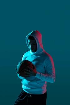 Großer mann, der basketball mit kühlen lichtern spielt