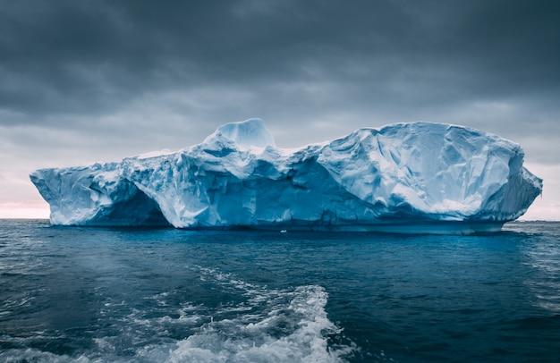 Großer massiver eisberg, der auf dem ozean schwimmt