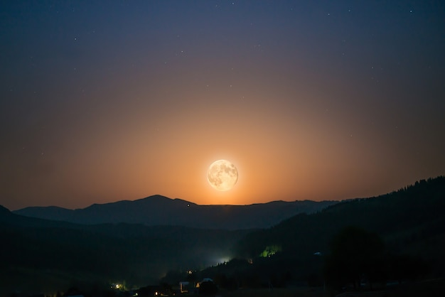 Großer mond am nachthimmel mit vielen sternen über der bergkette