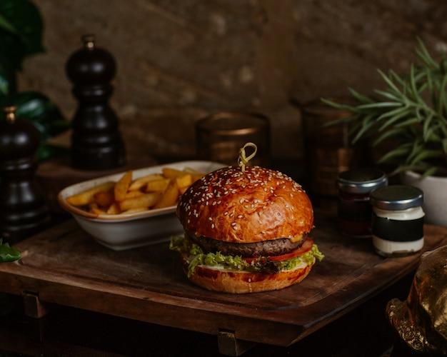 Großer portionsrindfleischburger mit pommes-frites und dip-sauce in einem café