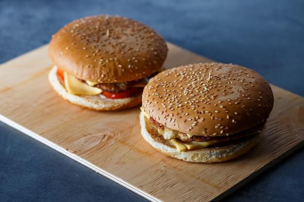 Großer saftiger burger mit schnitzelkäse und tomaten. fastfood.