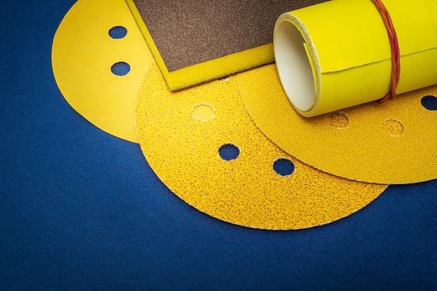 Großer satz gelber schleifwerkzeuge und schleifpapier auf blauem raum