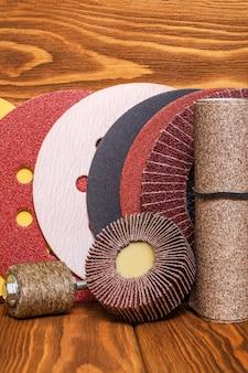 Großer satz schleifwerkzeuge und buntes sandpapier auf vintage-holzbrettern