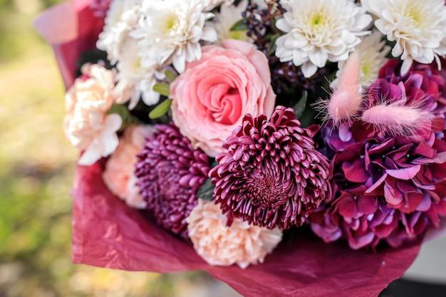 Großer schöner blumenstrauß der gemischten blumen in der frauenhand. blumengeschäftskonzept. schönes frisches bouquet. blumenlieferung. hochwertiges foto