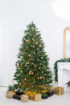 Großer schöner weihnachtsbaum geschmückt mit schönen glänzenden schmuckstücken und vielen verschiedenen geschenken auf dem boden.