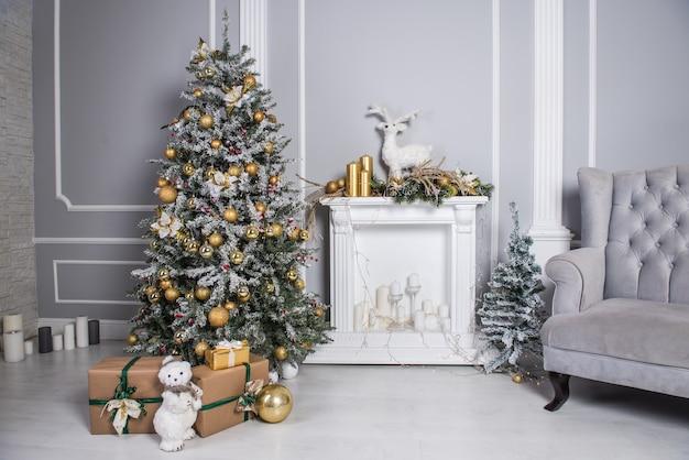 Großer schöner weihnachtsbaum oder neujahrsbaum mit kamin und geschenken in einem weißgrau dekorierten raum