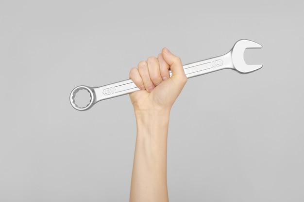 Großer schraubenschlüssel in der hand der frau. hand hält einen schraubenschlüssel auf einem grauen hintergrund.