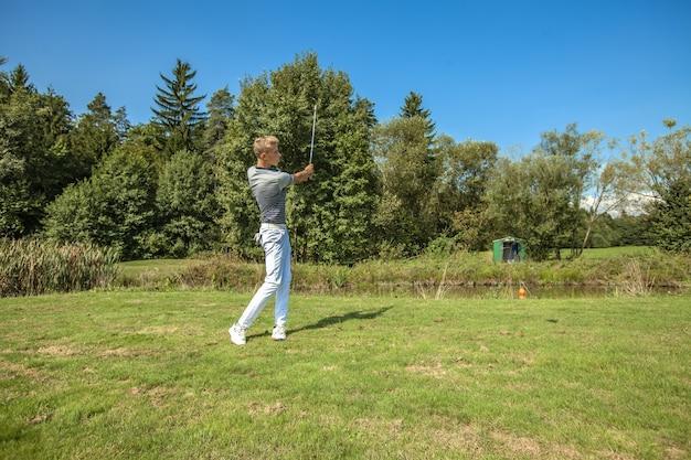 Großer schuss eines jungen mannes, der golf in einem feld spielt, das an einem sonnigen tag von bäumen umgeben ist