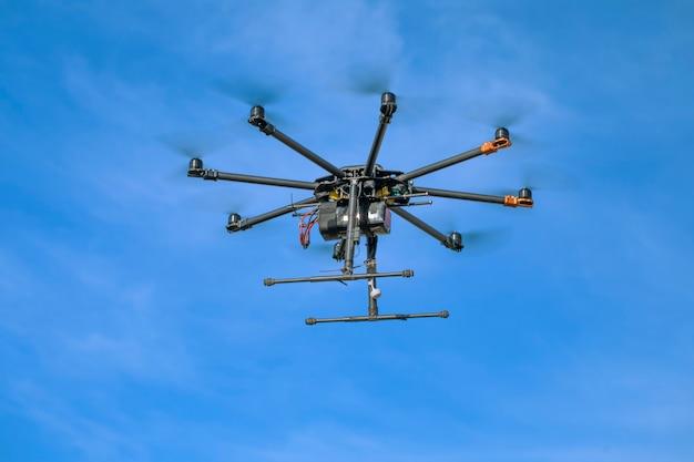 Großer schwarzer hausgemachter mächtiger hexacopter auf einer oberfläche des blauen himmels, nahaufnahme