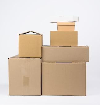 Großer stapel geschlossener brauner pappkartons des kartons auf weißem hintergrund, bewegendes konzept
