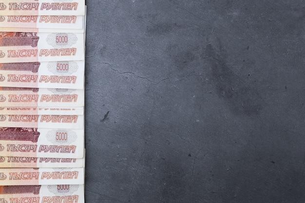 Großer stapel russische geldbanknoten von fünftausend rubeln liegend auf einem grauen zement.