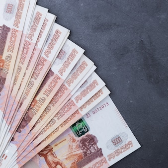 Großer stapel russische geldbanknoten von fünftausend rubeln liegend auf grauem zement