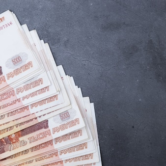Großer stapel russische geldbanknoten von fünftausend rubeln lügenfan auf einem grauen zementhintergrund.