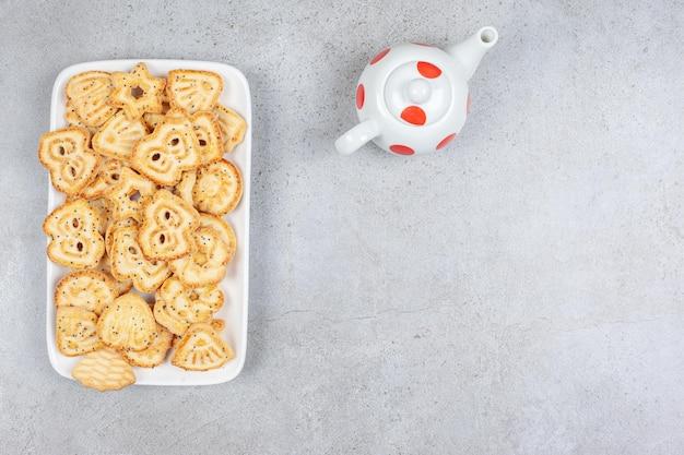 Großer stapel von kekschips auf einer platte neben einer kleinen teekanne auf marmorhintergrund. hochwertiges foto