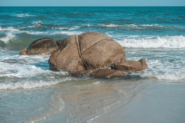 Großer stein mit seewelle auf dem hua hin-strand, prachuap khiri khan, thailand. pastellton.